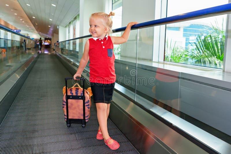 I flygplatsbarn med bagage gå för att hyvla logiporten royaltyfria foton