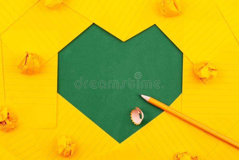 I fogli di carta arancio, la matita e le carte sgualcite si trovano su un consiglio scolastico verde e formano una forma del cuor immagine stock libera da diritti