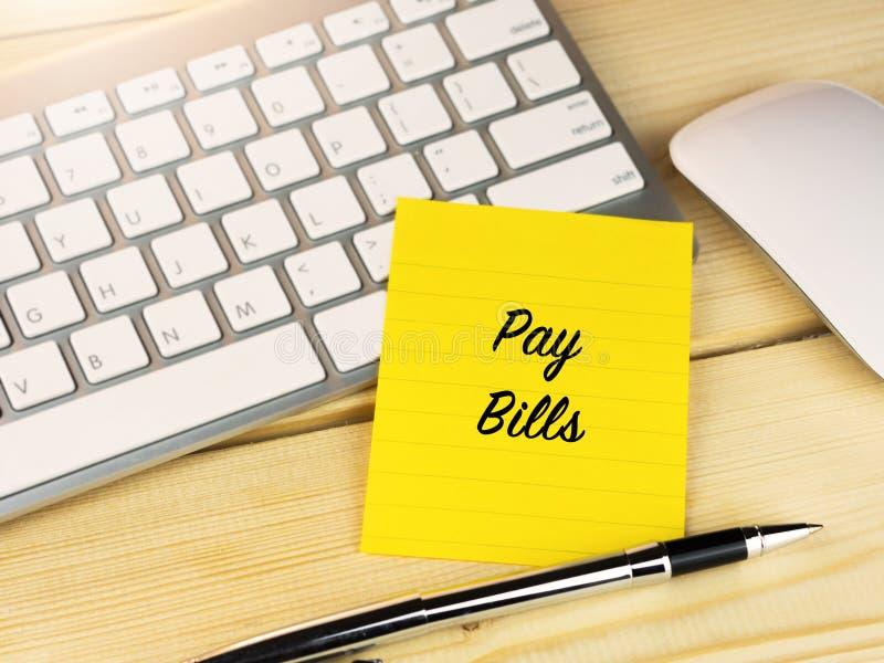 I fogli paga mandano un sms a sulla nota appiccicosa sullo scrittorio del lavoro, raggiro di ricordo di pagamento fotografie stock