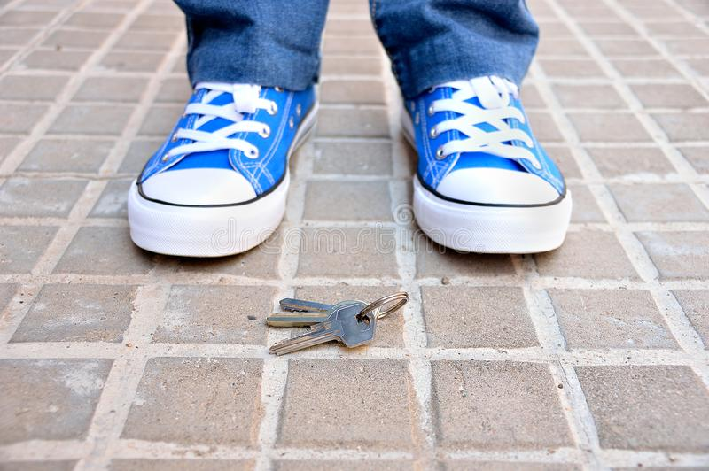 I found the keys. Young man found the keys on the sidewalk of the street stock photo
