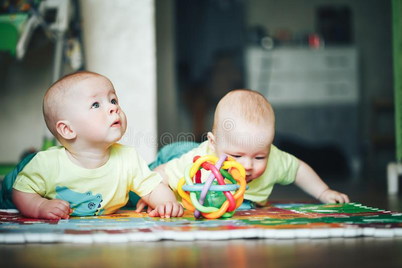 I fratelli di gemelli infantili del bambino del bambino sei mesi sta giocando sul pavimento immagine stock