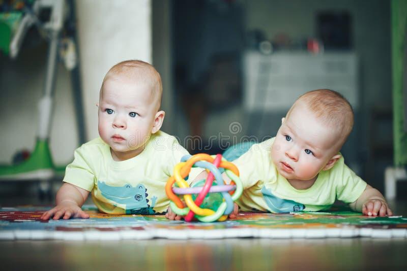 I fratelli di gemelli infantili del bambino del bambino sei mesi sta giocando sul pavimento immagine stock libera da diritti