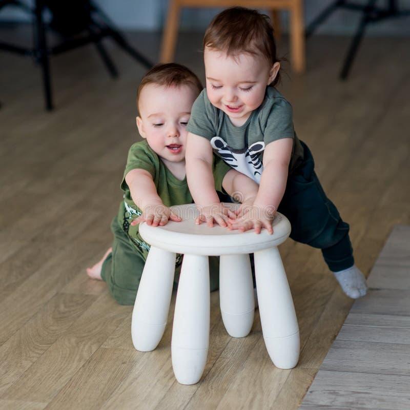 I fratelli gemelli di due anni giocano una piccola sedia immagine stock libera da diritti