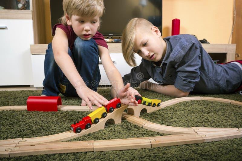 I fratelli giocano con il treno, la ferrovia del giocattolo di configurazione a casa o la d di legno fotografia stock