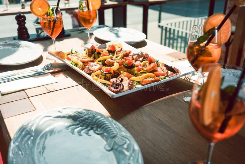 I frutti di mare freschi sono servito con i cocktail arancio sulla tavola di un ristorante d'avanguardia fotografie stock