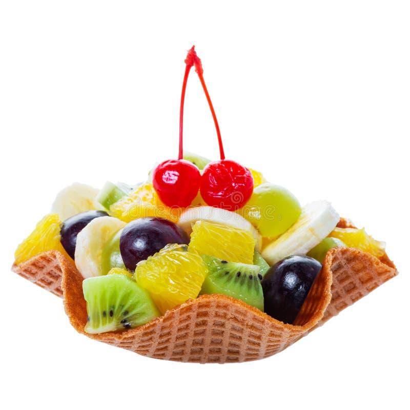 I frutti tagliati freschi nella ciliegia di maraschino decorata ciotola del cono della cialda sulla cima sono isolati su fondo bi immagini stock