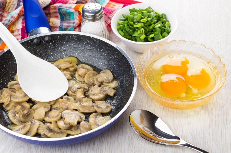 I funghi fritti, le uova crude del pollo, sale, hanno tagliato la cipolla di inverno a pezzi, sale, fotografia stock