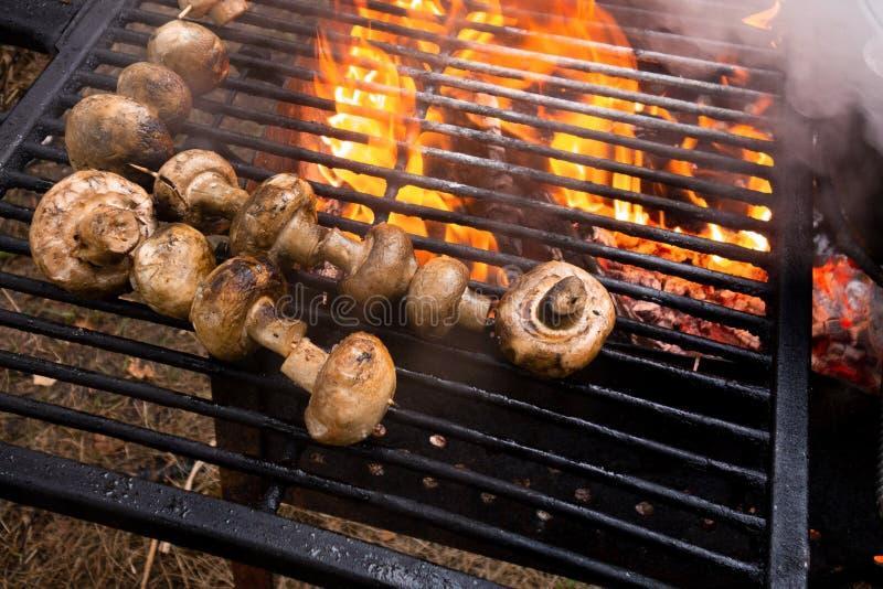 I funghi grigliano I funghi prataioli sono fritti o cotti su fuoco aperto Fine del partito della cucina del barbecue sull'immagin fotografia stock libera da diritti