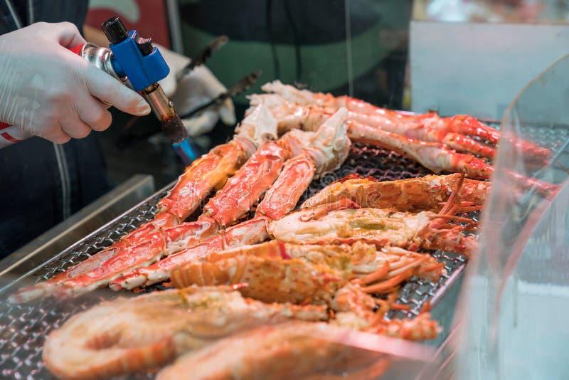 I gamberetti arrostiti ed il granchio sulla griglia sono fuoco e cucinato nel mercato ittico, Giappone fotografia stock libera da diritti