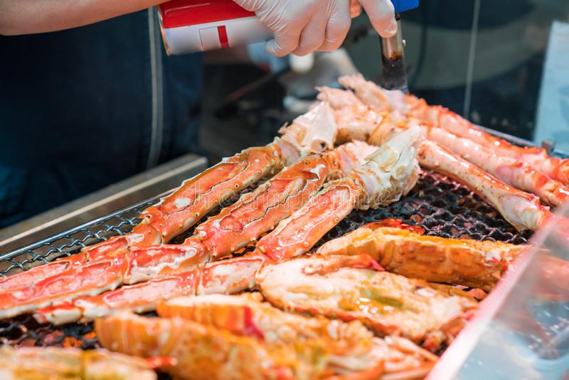 I gamberetti arrostiti ed il granchio sulla griglia sono fuoco e cucinato nel mercato ittico, Giappone fotografie stock libere da diritti