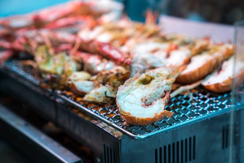 I gamberetti arrostiti ed il granchio sulla griglia sono fuoco e cucinato nel mercato ittico, Giappone immagine stock