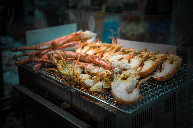 I gamberetti arrostiti ed il granchio sulla griglia sono fuoco e cucinato nel mercato ittico, Giappone immagine stock libera da diritti