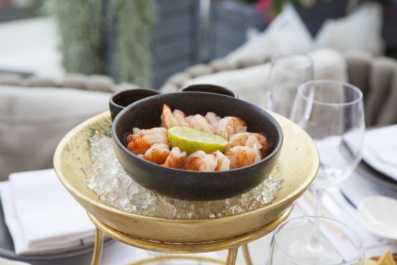 I gamberetti con calce in una ghisa lanciano nel ghiaccio su una tavola in un ristorante immagini stock libere da diritti