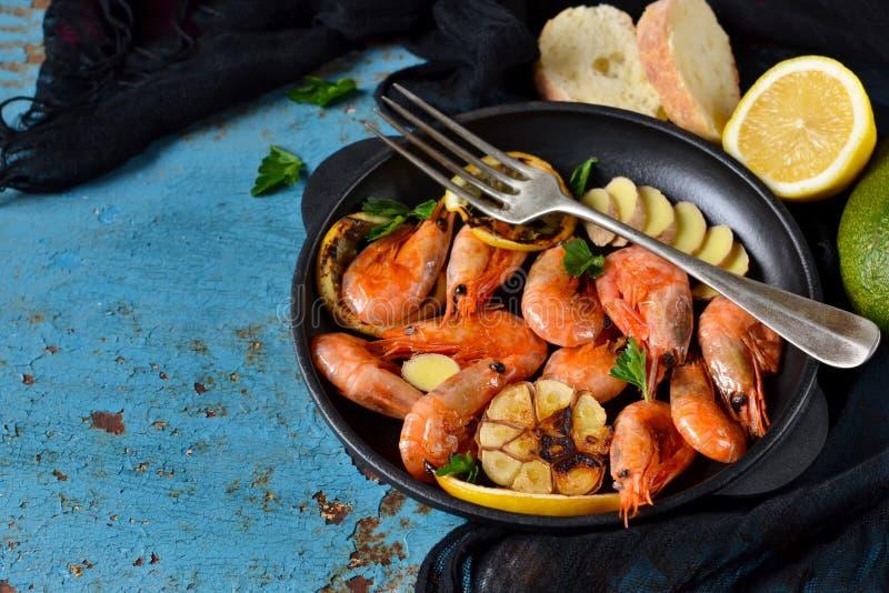 I gamberetti fritti della tigre con aglio ed il limone sauce su una ghisa f fotografia stock