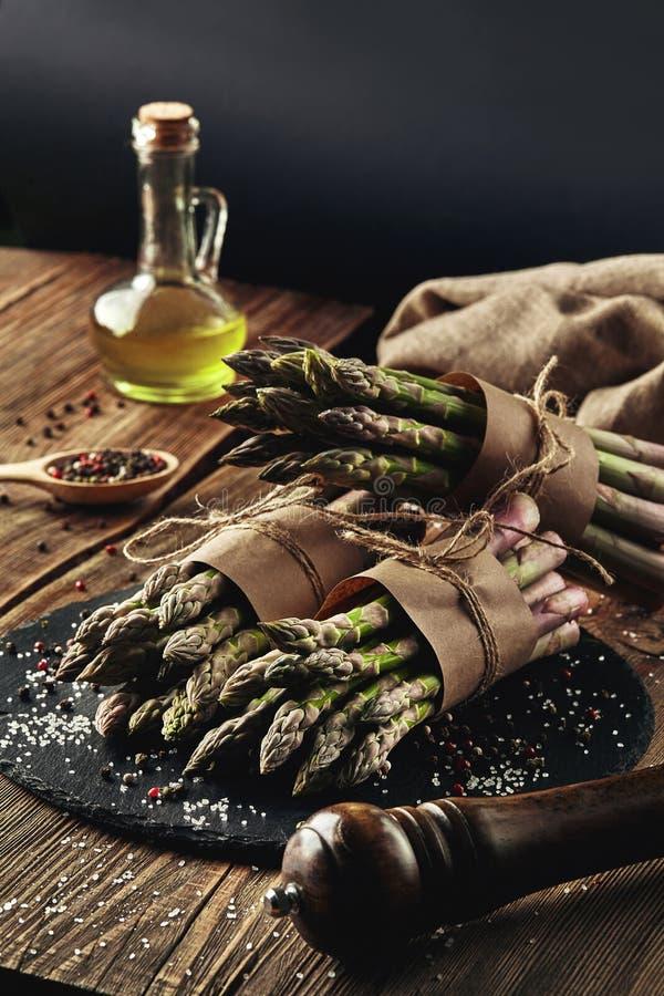 I gambi commestibili e crudi di asparago su un fondo di legno immagine stock