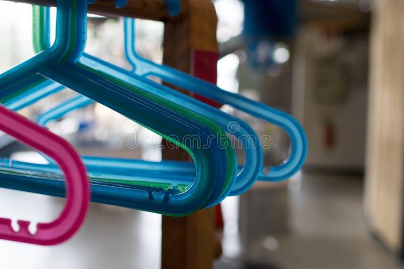 I ganci di plastica colorati hanno appeso su una struttura di legno Piccolo hange del bambino immagini stock