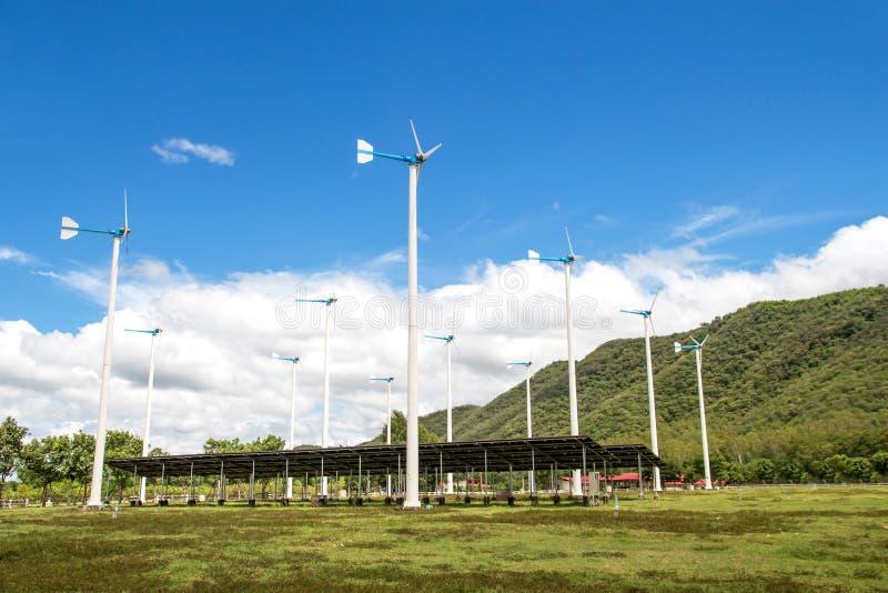 I generatori eolici con i pannelli solari coltivano sul agai del paesaggio di mountanis fotografia stock