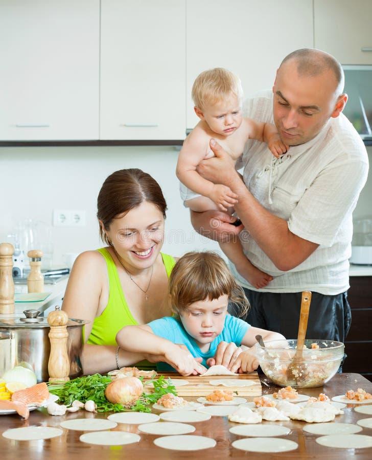 I genitori con gli gnocchi dei bambini pescano la cottura in una cucina domestica immagini stock