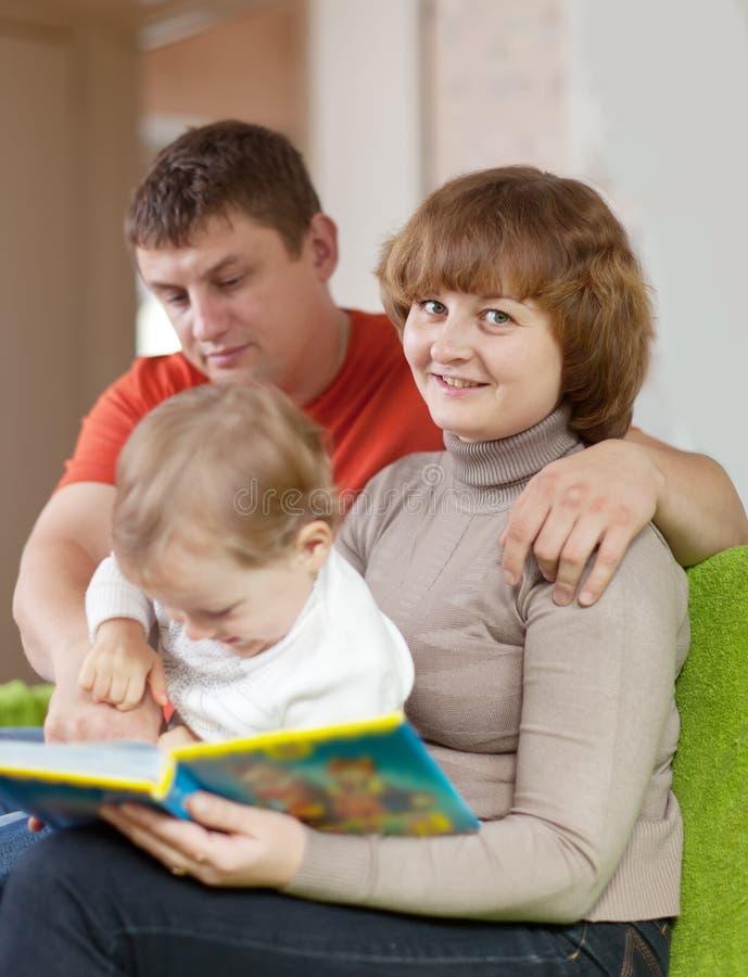 I genitori con il bambino osserva il libro fotografie stock libere da diritti