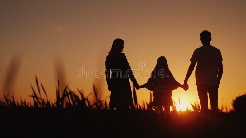 I genitori con il bambino stanno in un posto pittoresco, pieno d'ammirazione l'alba Sorelle che tengono le mani Concetto 'nucleo  immagini stock