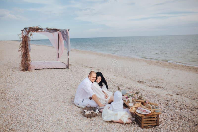 I genitori con un bambino si siedono a terra il mare immagini stock