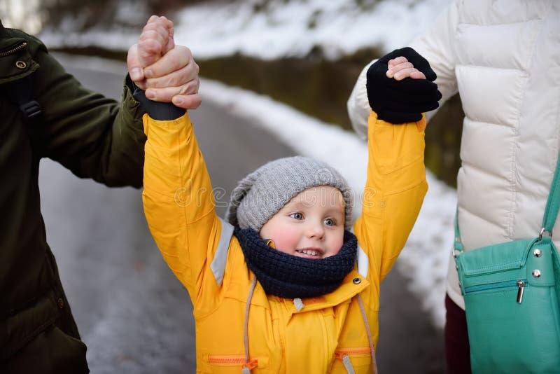 I genitori del bambino lo sollevano nell'aria dalle sue mani fotografia stock