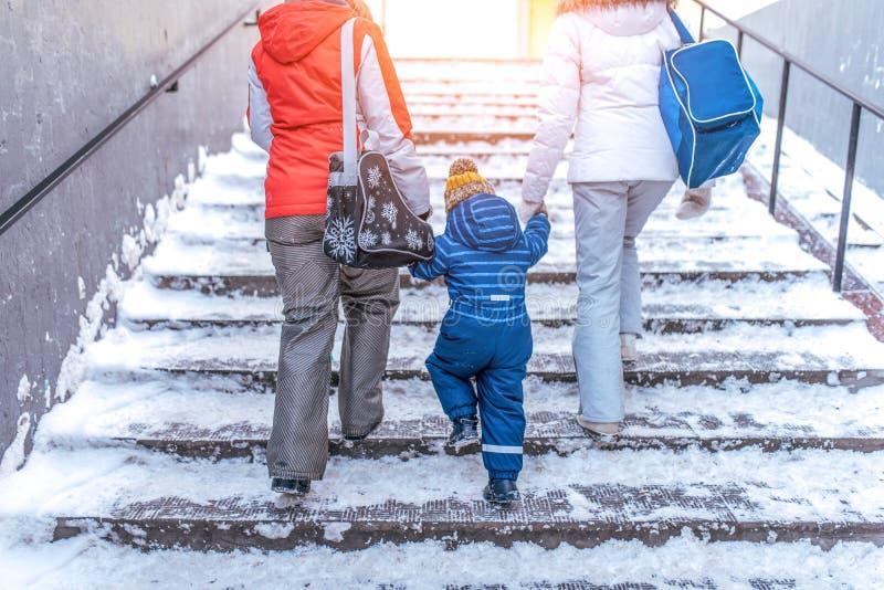 I genitori mamma ed il figlio del ragazzino della mano della tenuta della ragazza dell'amica 3-6 anni, salgono le scale nella tra fotografia stock
