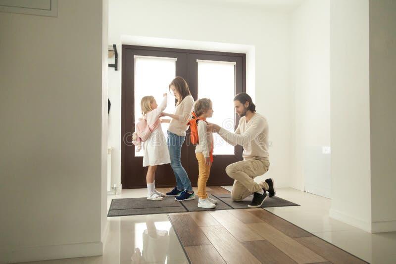 I genitori ottengono i bambini pronti per la passeggiata della scuola che sta al corridoio immagini stock