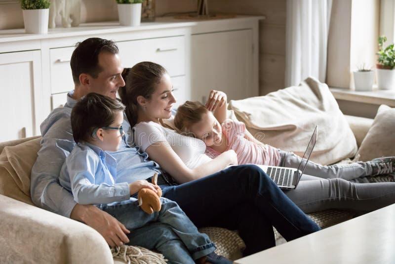 I genitori stringono a sé con i bambini che guardano il video del bambino al computer portatile immagine stock