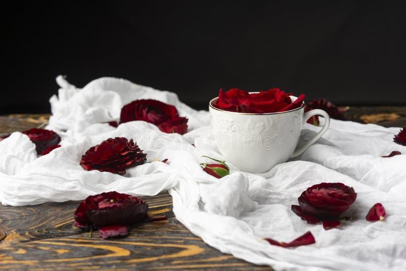 I germogli delle rose rosse, una di cui è in una tazza, bugia su un crumpl fotografia stock