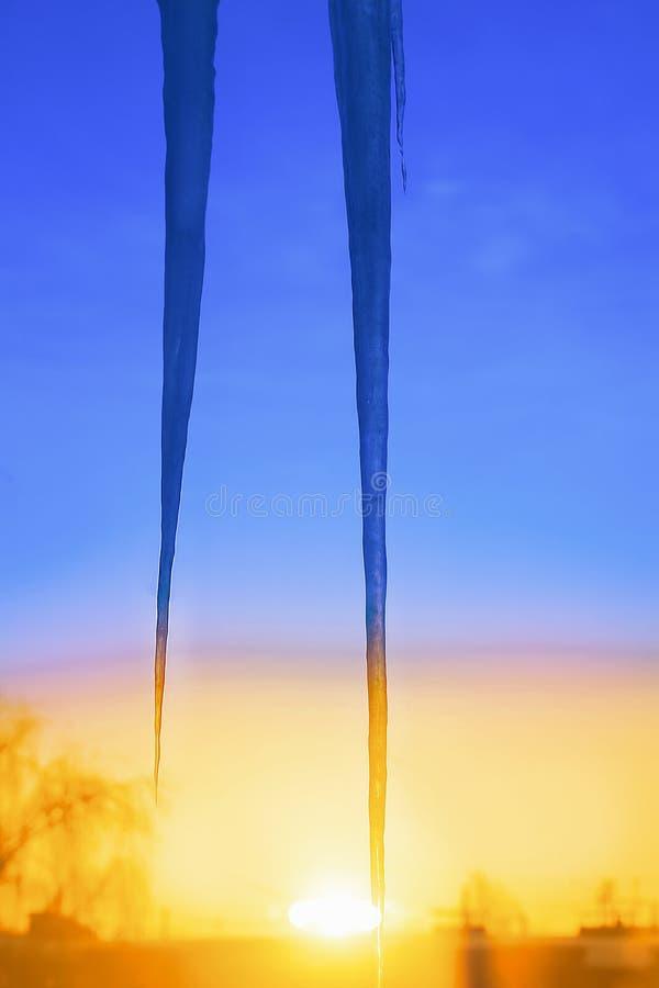 I ghiaccioli pendono dal tetto contro il cielo blu dell'inverno fotografia stock
