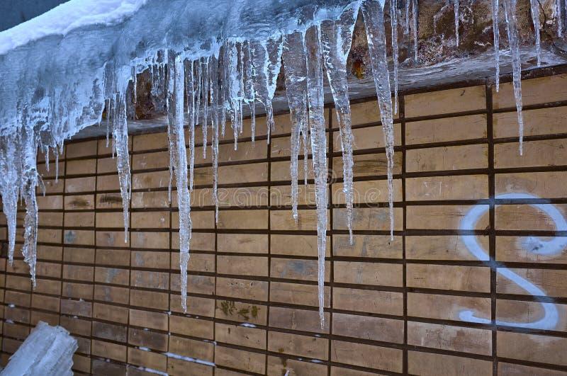 I ghiaccioli pendono dal tetto di vecchia parete, dell'inverno tardo o della primavera in anticipo fotografia stock libera da diritti