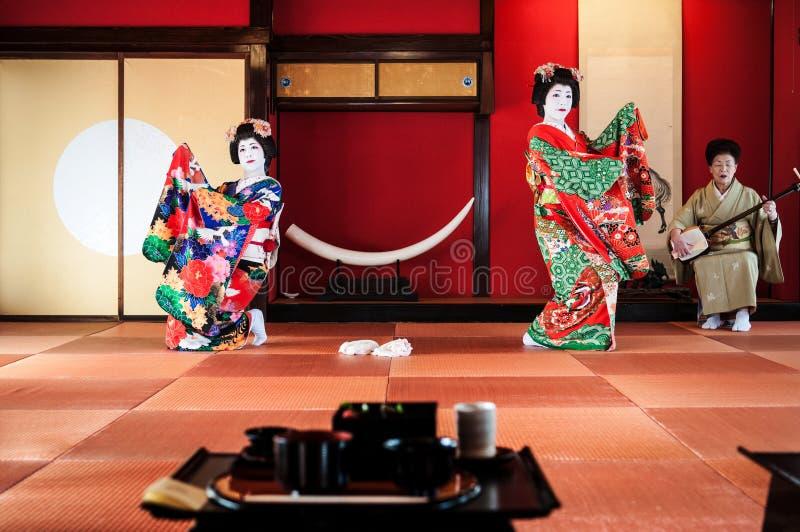 I giapponesi Maiko, geisha eseguono la manifestazione di dancing nel giapponese Tatami fotografia stock libera da diritti