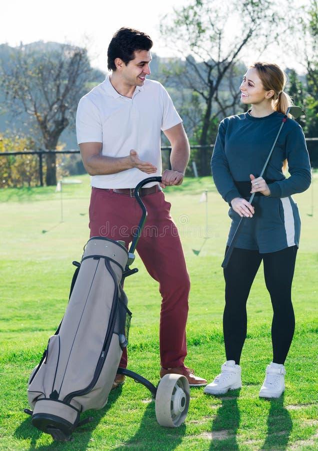 I giocatori di golf maschii e femminili pronti per il gruppo giocano al campo da golf fotografia stock