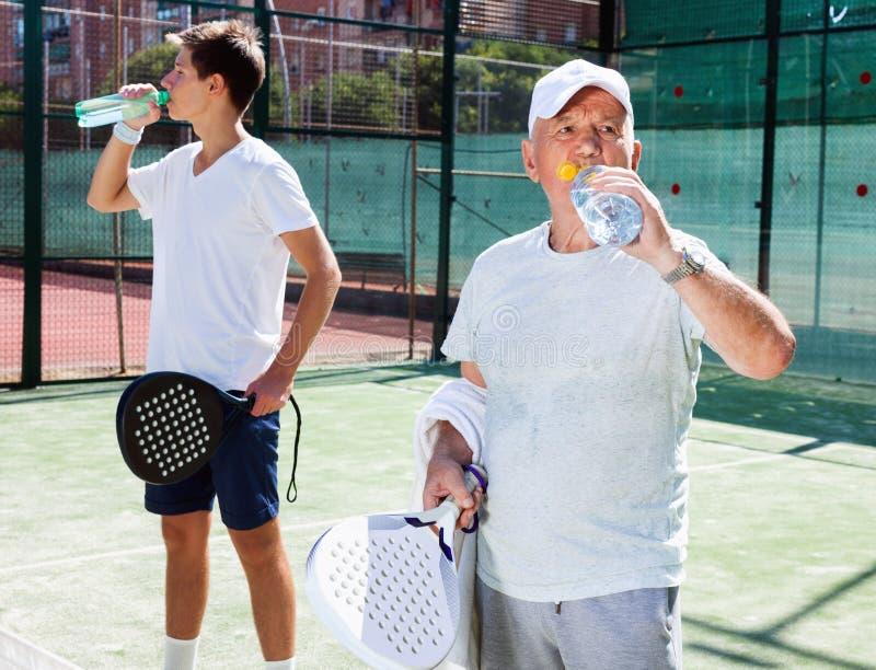 I giocatori di Padel di diverse generazioni bevono l'acqua in tribunale immagine stock libera da diritti