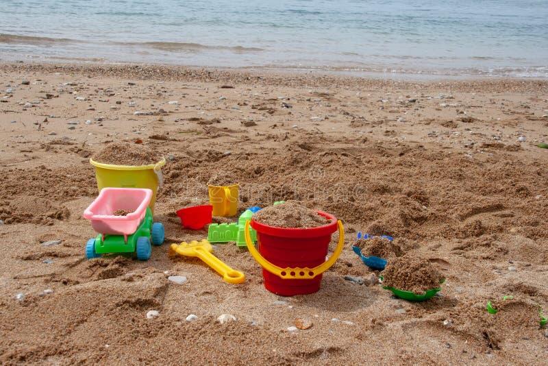 I giocattoli dei bambini di plastica intelligenti nella sabbia Concetto di ricreazione della spiaggia per i bambini immagini stock