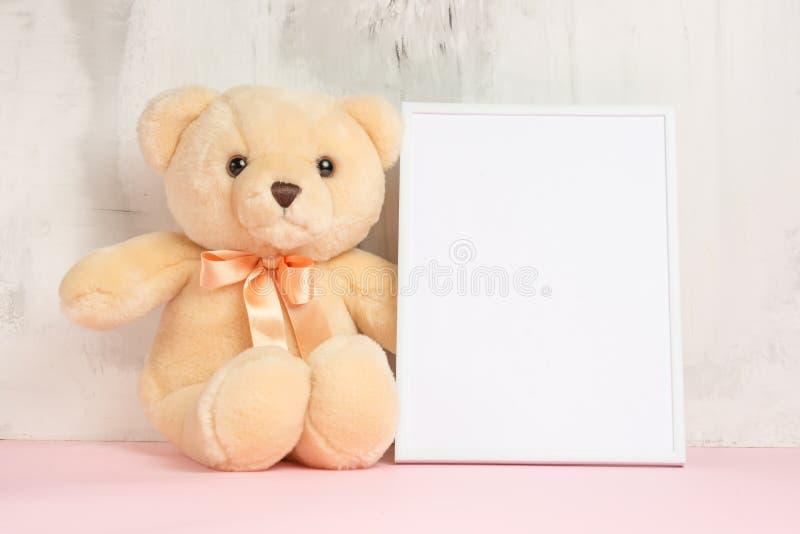 I giocattoli dei bambini, un orsacchiotto e una struttura su un fondo leggero della parete, per progettazione, disposizione Acqua fotografia stock