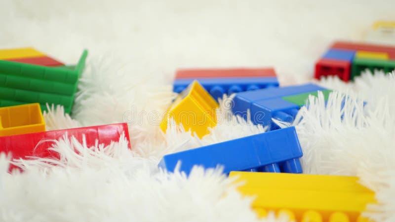 I giocattoli dei blocchetti di colore si trovano su un primo piano bianco del fondo Movimento del cursore della macchina fotograf immagini stock libere da diritti
