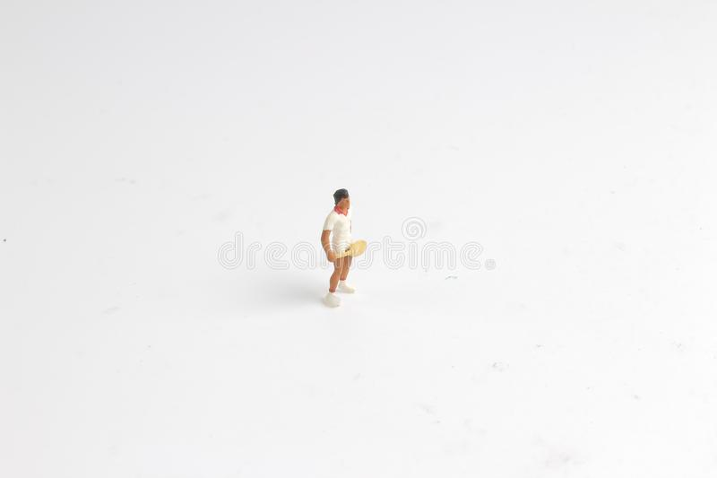 I giocattoli minuscoli giocano a tennis sul bordo bianco fotografie stock
