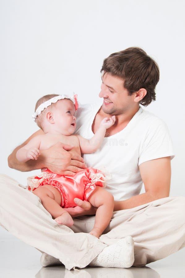 I giochi con il papà, il padre gettano sulla figlia del bambino in armi immagini stock