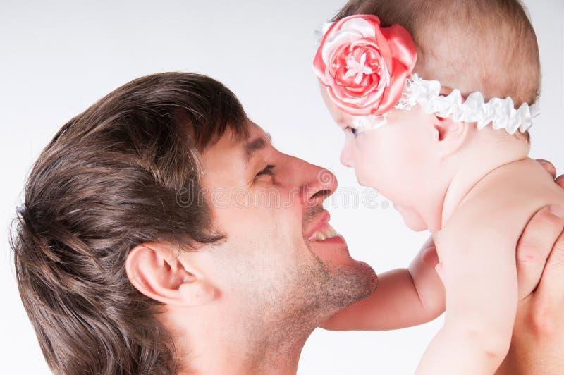 I giochi con il papà, il padre gettano sulla figlia del bambino in armi fotografie stock libere da diritti
