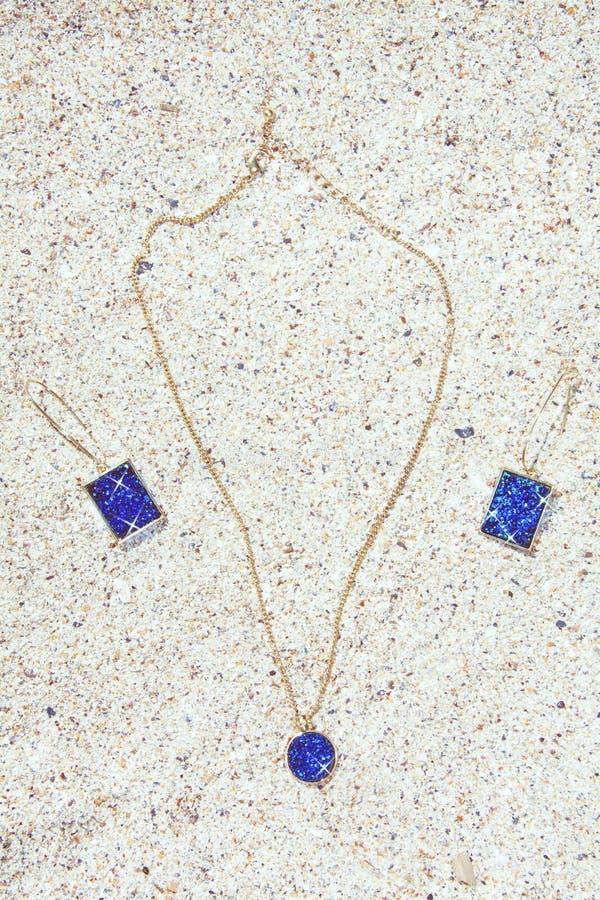 I gioielli hanno messo in tonalità acquatiche e nelle forme geometriche sul fondo della spiaggia di sabbia fotografie stock