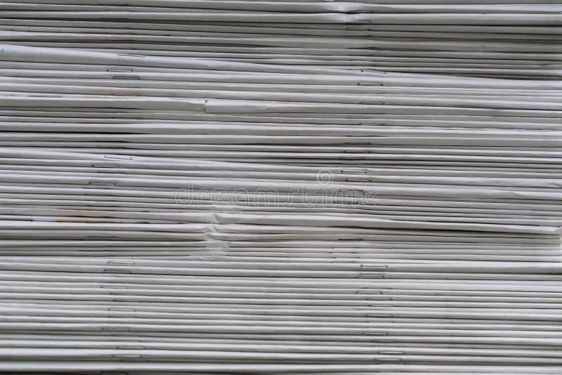 I giornali hanno piegato ed impilato il fondo sulla tavola immagine stock