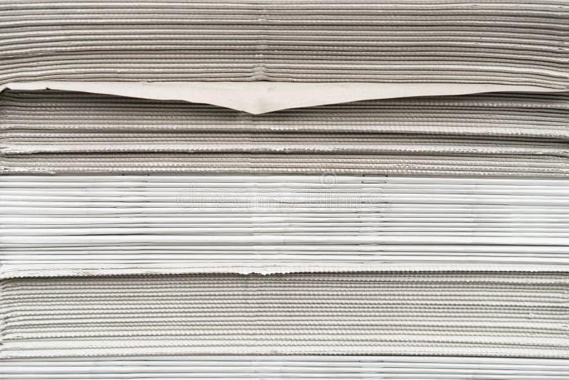 I giornali hanno piegato ed impilato il fondo sulla tavola fotografia stock