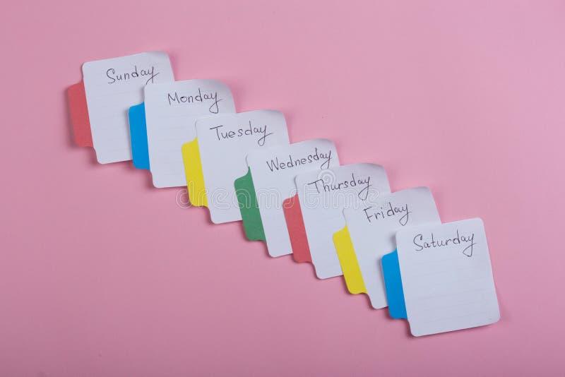 I giorni della settimana - gli autoadesivi di carta allegati ai precedenti rosa è immagine stock libera da diritti