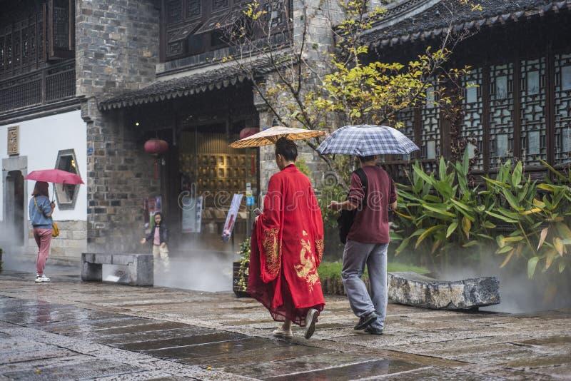I giorni piovosi, due turisti con gli ombrelli hanno camminato attraverso il punto scenico, uno di loro che portano un abito anti immagini stock libere da diritti