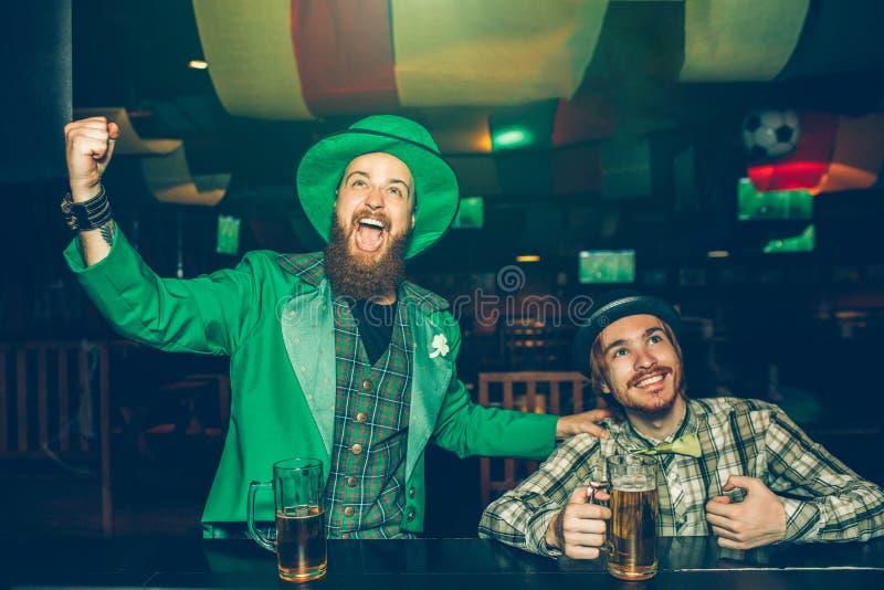 I giovani allegri si siedono al contatore della barra in pub e nell'incoraggiare Guardano in avanti I tipi hanno tazze della birr fotografie stock libere da diritti