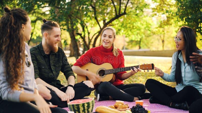 I giovani allegri sono cantanti e muoventi le mani quando la bella ragazza sta giocando la chitarra durante il picnic in parco so immagini stock