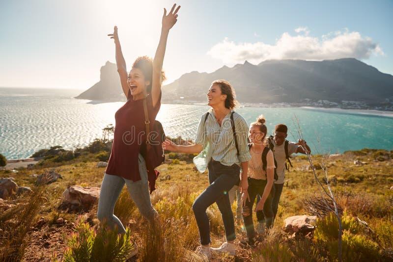 I giovani amici adulti che fanno un'escursione il singolo archivio in salita celebrano il raggiungimento della sommità, vista lat fotografie stock libere da diritti