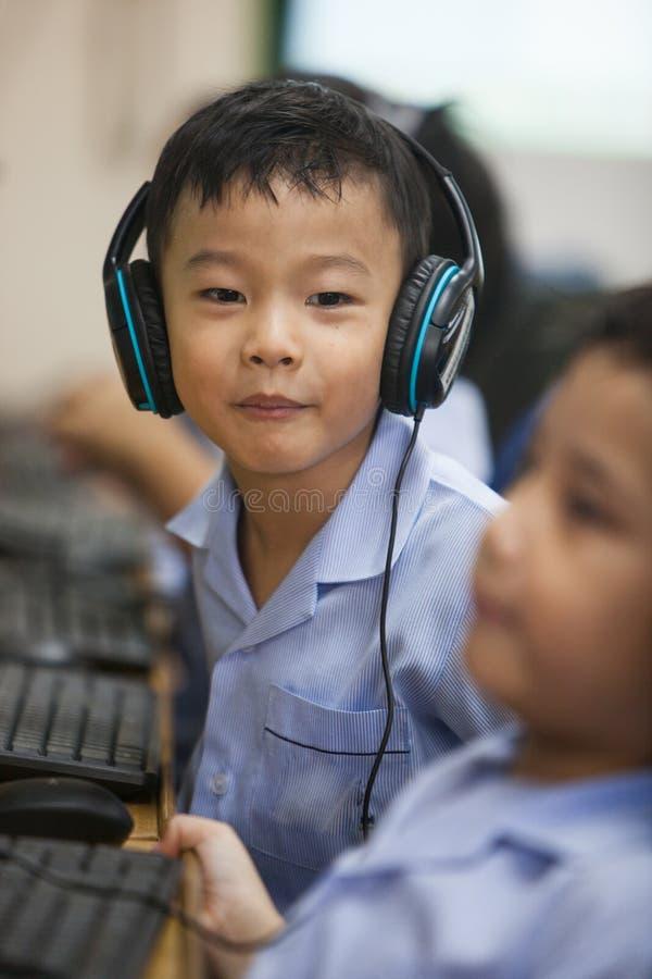 I giovani bambini della scuola cominciano imparare come utilizzare un computer fotografia stock